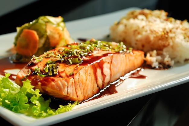 Comida japonesa salmón a la parrilla con arroz en un plato cuadrado blanco fondo borroso