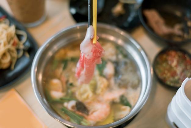 Comida japonesa de shabu con deliciosa carne de res en rebanadas, cocción en sopa hervida caliente