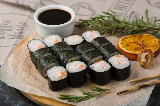 Comida japonesa de sushi. enrolle en nori con arroz, cangrejo de nieve y caviar.