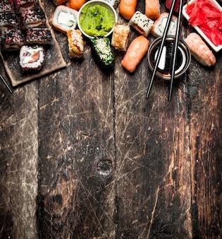 Comida japonesa. sushi y rollos de mariscos frescos con salsa de soja. en el fondo de madera vieja.