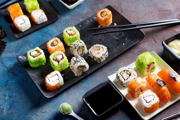 Comida japonesa: sushi, rollos, palillos, salsa de soja sobre fondo de piedra