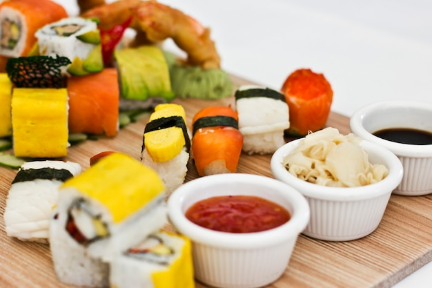 Comida japonesa - sushi, sashimi, rollos en una tabla de madera. aislado