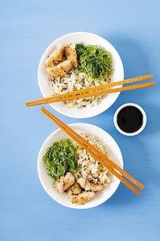 Comida japonesa. tazón de arroz, pescado blanco hervido y ensalada de wakame chuka o algas. vista superior. lay flat