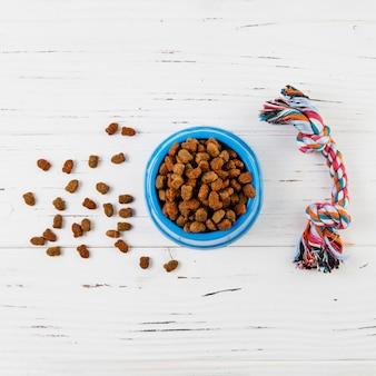 Comida y juguete para perros en superficie de madera blanca.