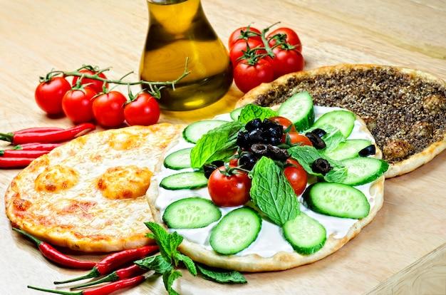 Comida libanesa de tomou y queso manouche aislado en la tabla.