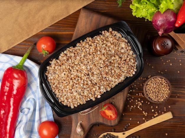 Comida para llevar del alforfón en el envase de plástico negro, alimento dietético.