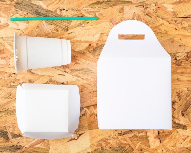 Comida para llevar blanca con pajita turquesa sobre fondo de madera