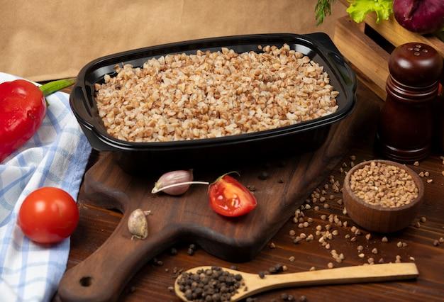 Comida para llevar de trigo sarraceno en un recipiente de plástico negro.
