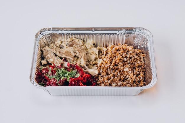 Comida para llevar con verduras y carne en cajas.
