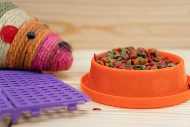 Comida para mascotas con juguete y tapete de plástico.