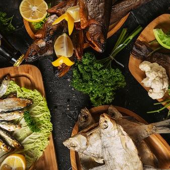 Comida mediterránea, pescado de arenque ahumado servido con cebolla verde, limón, tomates cherry, especias, pan y salsa tahini en la oscuridad. vista superior con un primer plano