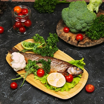 Comida mediterránea, pescado de arenque ahumado servido con cebolla verde, limón, tomates cherry, especias, pan y salsa tahini.