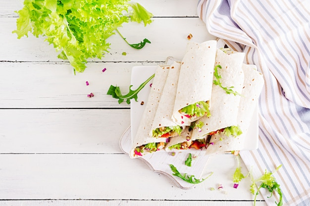 Comida mexicana de calle, fajita, tortilla con envoltura de pollo a la parrilla y verduras frescas. vista superior