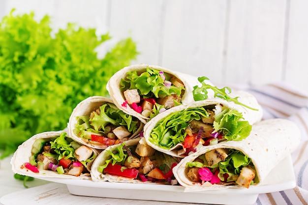 Comida mexicana de calle, fajita, tortilla con envoltura de pollo a la parrilla y verduras frescas.