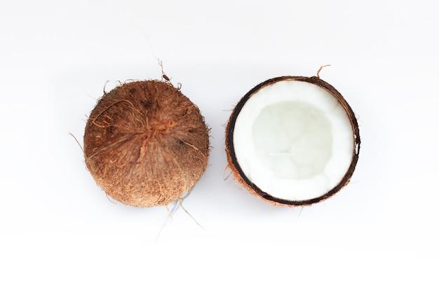 Comida, minimalismo, color, naturaleza muerta y concepto natural: cocos maduros y medio coco sobre fondo blanco.