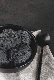 Comida de moda. helado negro con sésamo negro, en un tazón negro