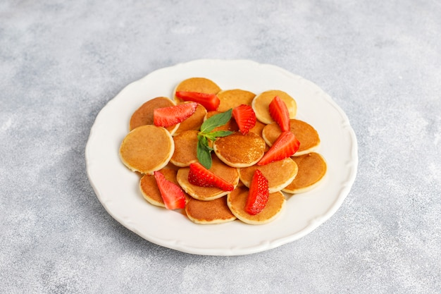 Comida de moda: mini cereal para panqueques. montón de panqueques de cereales con bayas y nueces.