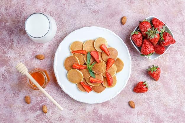 Comida de moda: mini cereal para panqueques. montón de panqueques de cereales con bayas