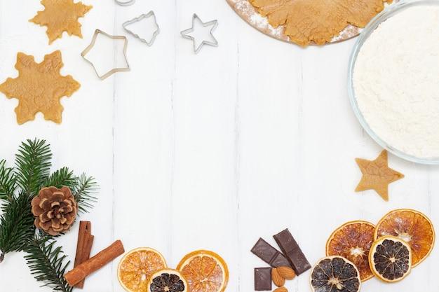 Comida navideña. copyspace galletas de jengibre caseras con ingredientes para hornear navidad y utensilios de cocina en una mesa blanca