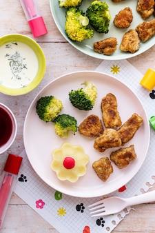 Comida para niños, nuggets de pollo y brócoli.