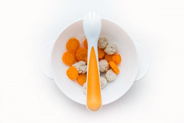 Comida para niños, primer señuelo para bebés, trozos de zanahoria y pavo en un plato