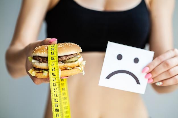 Comida nociva, la elección entre comida maliciosa y deporte, hermosa joven a dieta, el concepto de belleza y salud, sobre un fondo gris