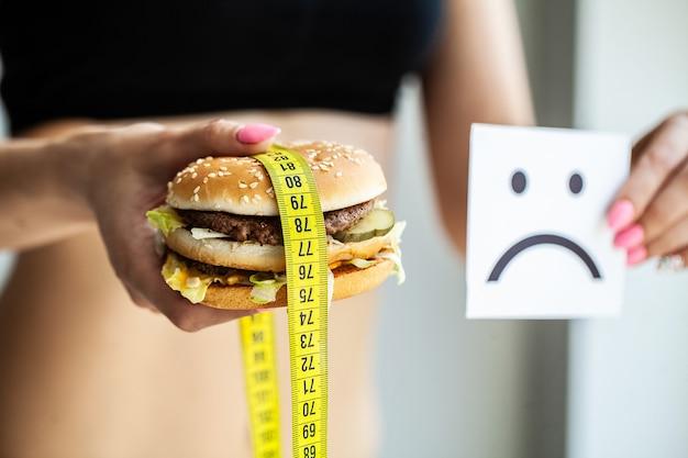 Comida nociva, la elección entre comida maliciosa y deporte, hermosa joven a dieta,