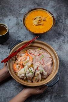 Comida del norte de tailandia (khao soi ruam), sopa de fideos picantes decorada con ingredientes.