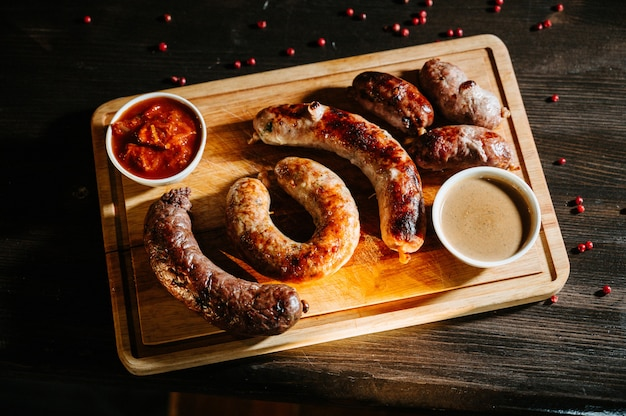 Comida oktoberfest, apetitosas salchichas de carne. un gran surtido en una bandeja de madera.