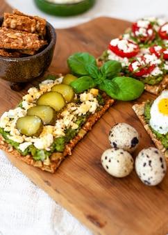 Comida orgánica saludable con tostadas de aguacate con queso griego y pepino y una ramita de albahaca.