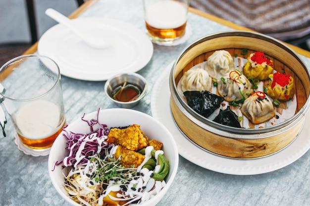 Comida panasiática: diferentes sumas oscuras en tazón de bambú y ensalada. almuerzo para dos con cerveza.