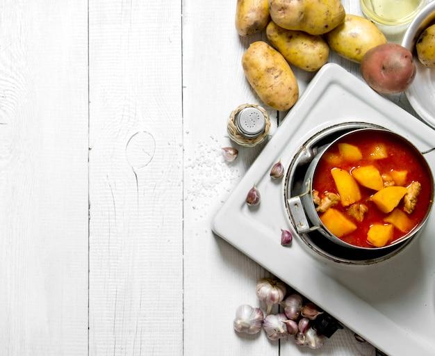 Comida de patata. patatas guisadas con carne y especias en una cocina eléctrica sobre mesa de madera blanca. espacio libre para texto. vista superior