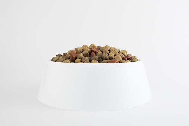 Comida para perro o gato. comida seca para gatitos o cachorros de cerca en un recipiente blanco sobre un blanco