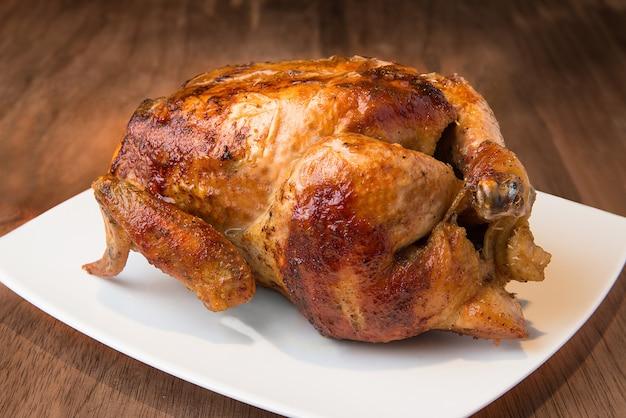 Comida peruana delicioso pollo a la parrilla entero sobre textura de madera