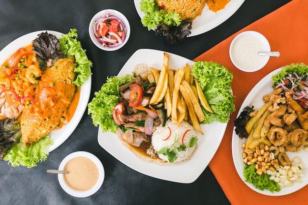 Comida peruana, mariscos, papas fritas y salsas.