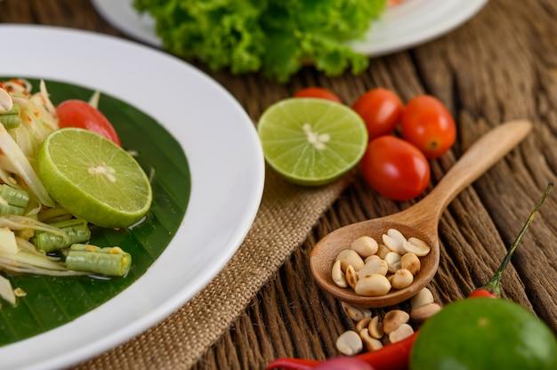 Comida picante de estilo tailandés, concepto de comida som tum, decoración de accesorios ajo, limón, maní, tomate y chalotes en la mesa de madera