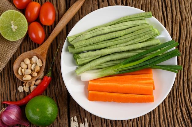 Comida picante de estilo tailandés, concepto de comida som tum, decoración de utilería ajo, limón, tomate, chile, frijoles, cebolletas, chalotes y zanahorias y cacahuetes en la cuchara de madera en la mesa de madera.
