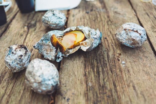 La comida del picnic. patatas con manteca al horno en papel de aluminio, al fuego. vista superior, sobre una mesa de madera.