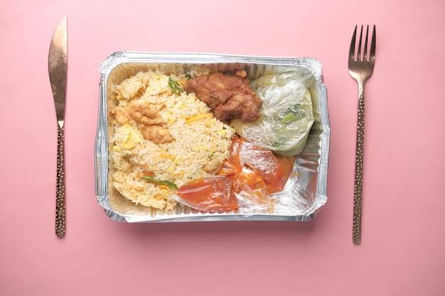 Comida de pollo biryani en una caja para llevar en la mesa