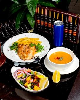 Una comida preparada con sopa de lentejas, pescado a la parrilla, papas fritas y ensalada de verduras.