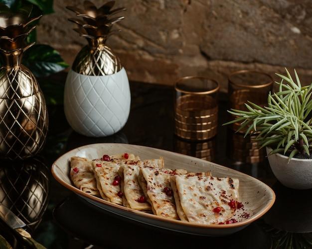 Comida rápida caucásica qutab, kutab, frito y servido con semillas de granada