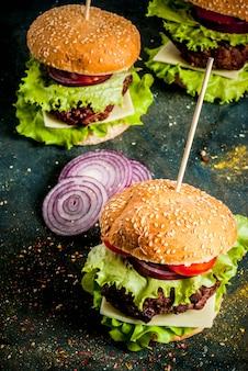 Comida rápida comida poco saludable deliciosa hamburguesa sabrosa fresca con chuleta de res verduras frescas y queso sobre fondo de hormigón azul oscuro