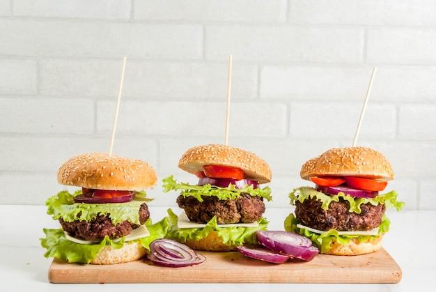 Comida rápida comida poco saludable deliciosas hamburguesas sabrosas frescas con chuleta de ternera verduras frescas y queso sobre fondo blanco