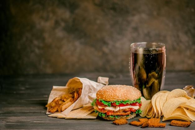 Comida rápida y concepto de alimentación poco saludable. sabrosa y apetitosa hamburguesa, cola y papas fritas