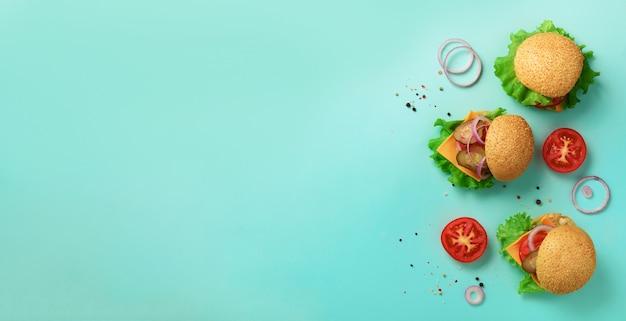 Comida rápida, concepto de dieta poco saludable. hamburguesas caseras jugosas, tomates, queso, cebolla, pepino y lechuga sobre fondo azul.
