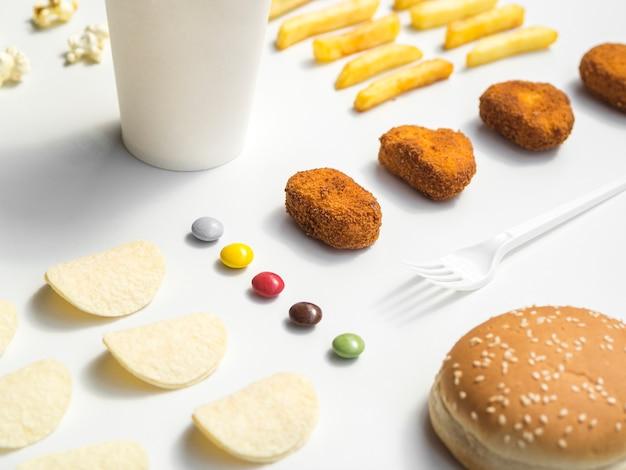 Comida rápida y dulces en mesa blanca
