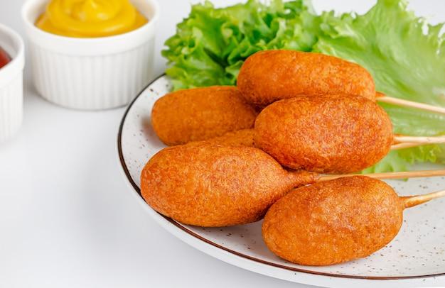 Comida rápida estadounidense. perros de maíz en la pared blanca con mostaza. comida chatarra y concepto de alimentación poco saludable