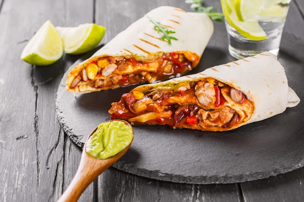 Comida rápida sabrosa: burritos mexicanos con salsa de guacamole sobre fondo de madera negro