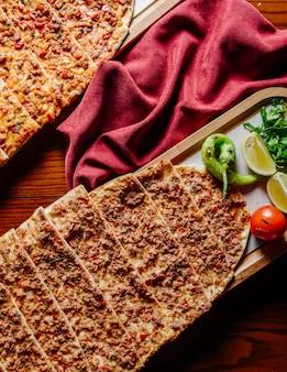 Comida rápida turca lahmacun servida con limón y verduras.