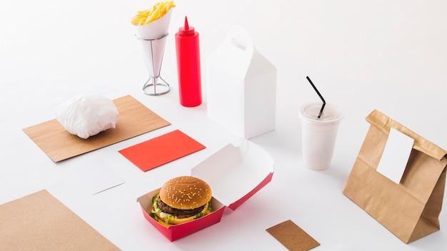 Comida rápida; vaso desechable; botella y paquete de salsa sobre fondo blanco